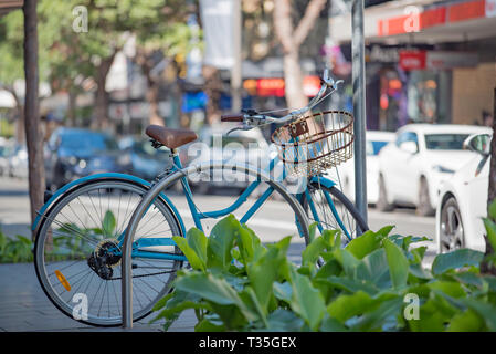 A bicycle parked next to a street garden on the footpath of busy Crown Street, Surry Hills in Inner Sydney, Australia - Stock Image