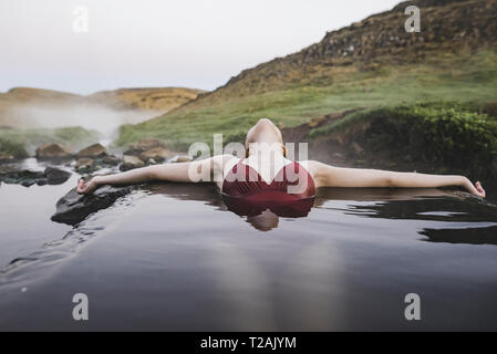 Woman bathing in hotpool in Iceland - Stock Image