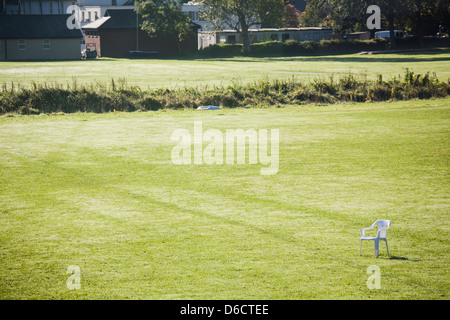 Empty playing field with one white plastic chair to the right, background buildings. Space,solitude,loneliness,peace,quiet,sport - Stock Image