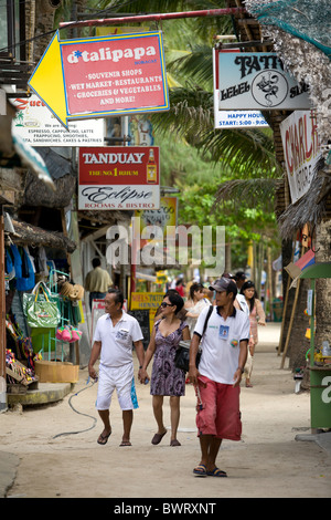 Tourists and locals walk along the vendor and restaurant-lined beach walk on Long Beach in Boracay, Philippines. - Stock Image