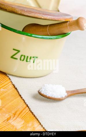 Coarse sea salt pot and wooden spoon - Stock Image