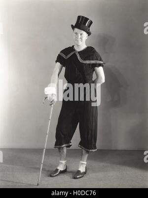 Man posing in cuffs, top hat and circus costume - Stock Image