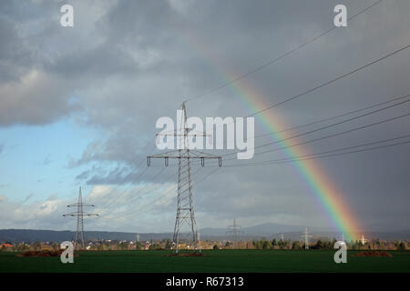 rainbow with high voltage power lines - Stock Image