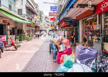 Bangkok, Thailand - April 21st 2011. Man packing boxes. This is a typical street in Chinatown. - Stock Image