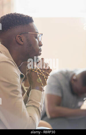 Serene young man praying with rosary in prayer group - Stock Image