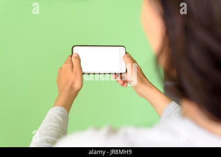 Woman holding a Smart Phone device with clipping path for VR augmented reality overlays - Stock Image