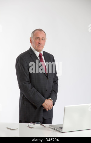 Portrait of a mature male office worker standing behind a white desk with a laptop open, glasses and iphone on the - Stock Image