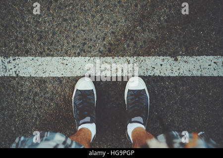 View of feet of man in white socks and gumshoes standing near grunge white line on gray asphalted road, ready to - Stock Image