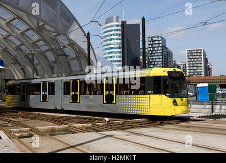Metrolink tram leaving Victoria Station, city centre, Manchester, UK. Green Quarter urban redevelopment buildings - Stock Image