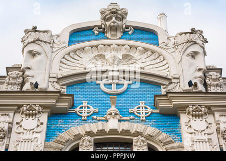 Riga art nouveau architecture, detail of a gable with huge sculpted heads and blue tiles sited in Elizabetes Iela in the Art Nouveau district of Riga. - Stock Image