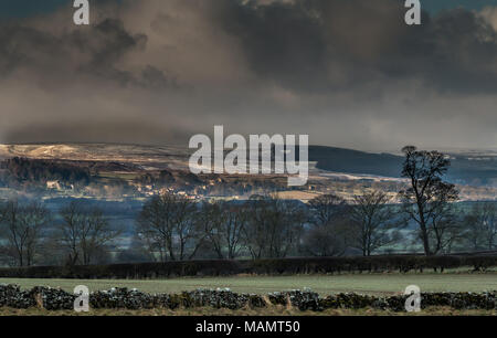 Teesdale landscape, a brief sunny interval highlights the rural conservation village of Barningham, with a fresh covering of snow on the moor behind - Stock Image