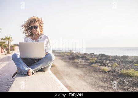 Technology and travel. Working outdoors. Freelance concept. Pretty young woman using laptop  beach. - Stock Image