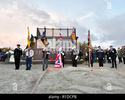 West Wittering Beach Commemorates Armistice Day -The Wittering Royal British Legion  take the salut when West Wittering Estate invited local residents and visitors to join them on Wittering beach to commemorate 100 years since the end of WWI. Inspired by Danny Boyle's 'Pages in the Sea' Ð a national art event  Location in front of local sculptor Alexandra Beale's  silhouette in the sand of Charles Henry Kewell, one of four brothers from the West Wittering Kewell family killed in the war.Contributor: Gary Blake / West Wittering Estate /Alamy Stock Photo - Stock Image