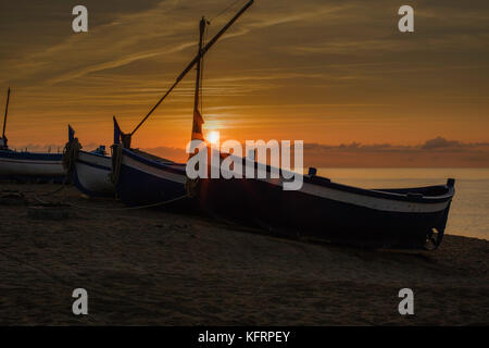 A small fisher boat on a dreamlike beach touched by the first sunrays - Stock Image