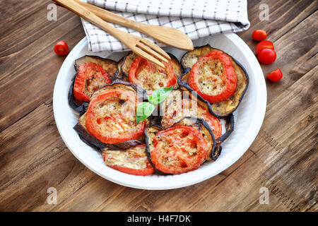 Baked eggplant with tomatoes as tasty vegetarian pizza topping, main course in a holiday day, traditional italian - Stock Image