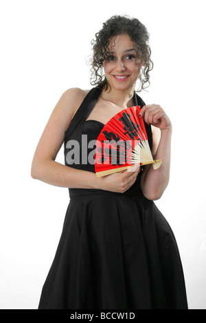 Dark Haired Portuguese Woman in a Black Dress with a Red Fan, White Background - Stock Image