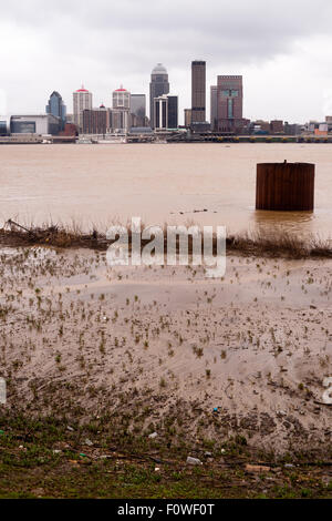 Spring rains flood the Ohio River banks along the shore of the largest city in Kentucky - Stock Image