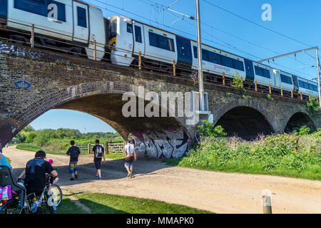 Class 379 Electrostar train crossing  railway arches used by A.V. Roe to assemble Roe 1 triplane in 1909, Walthamstow Marshes, London England - Stock Image