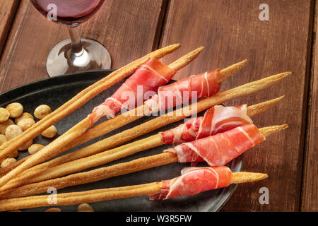 Prosciutto-wrapped Italian grissini with red wine and roasted almonds, close-up shot on a wooden background. Italian antipasti with parma ham - Stock Image