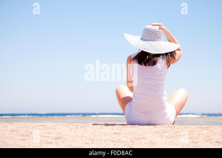 Young woman sitting on the sand at the beach - Stock Image