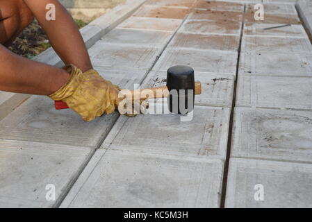 Man with a rubber mallet taps tiles on a pathway as part of a DIY construction project at home - Stock Image