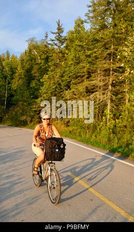 Woman bicycling on bike path that circles the entire Mackinac Island, a popular vechile-free (no cars) tourist destination in Michigan, USA. - Stock Image