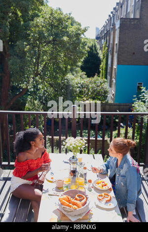 Young women friends enjoying brunch on sunny urban apartment balcony - Stock Image