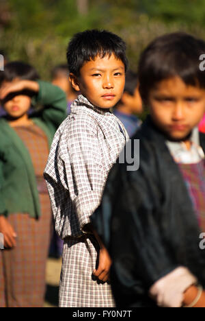 Students wearing traditional dress at morning assembly at a primary school in Nimshong village in southern Bhutan - Stock Image