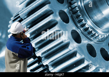 engineer, mechanic pointing at large gear machinery - Stock Image