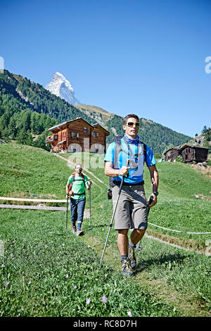 Hikers on lush green field, chalets in background, Mont Cervin, Matterhorn, Valais, Switzerland - Stock Image