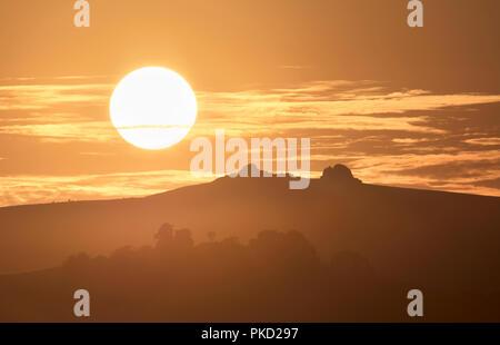 Silhouette of Haytor Rocks on Dartmoor with the setting sun - Stock Image