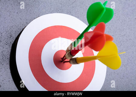 An Elevated View Of Colorful Darts On Target Against Gray Background - Stock Image