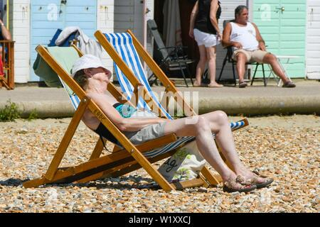 Lyme Regis, Dorset, UK.  4th July 2019. UK Weather.  A woman sunbathing on the beach at the seaside resort of Lyme Regis in Dorset enjoying a day of clear skies and scorching hot sunshine.   Picture Credit: Graham Hunt/Alamy Live News - Stock Image