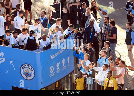 Manchester City's Fabian Delph and Oleksandr Zinchenko with the Premier League trophy on the bus as they pass the crowds of fans gathered on the route during the trophy parade in Manchester. - Stock Image