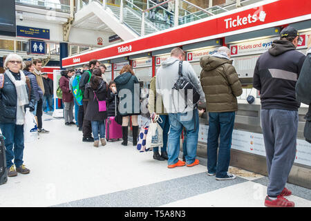 Travellers buying tickets on the concourse in Liverpool Street Station in London. - Stock Image