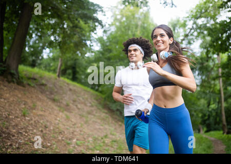 fitness, sport, friendship and lifestyle concept - smiling couple exercising outdoors - Stock Image