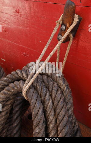 Belaying pin and coiled rope on a tall ship. - Stock Image