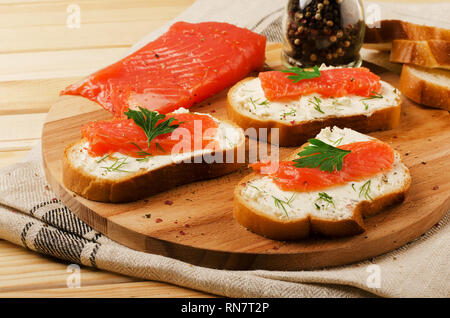 Appetizer with salmon and cottage cheese cream on a cutting board - Stock Image