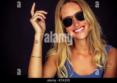Young woman wearing sunglasses, smiling cheerfully, portrait - Stock Image