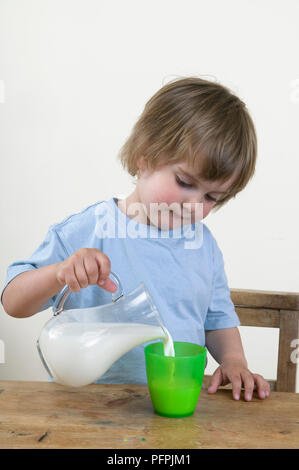 Young boy pouring himself a cup of milk from a jug - Stock Image