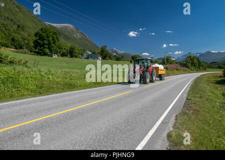 Tractor pulling a loaded trailer along a countryside road in Norway. - Stock Image