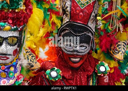 Dancers wearing colorful costumes at the Battle of Flowers - Stock Image