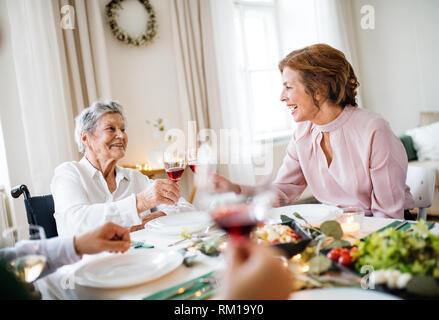 An elderly woman in wheelchair sitting at the table on a indoor party, clinking glasses. - Stock Image