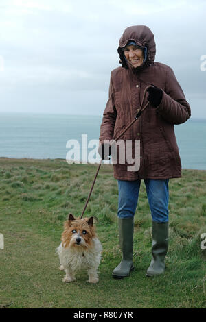 An old lady with her blind dog on a cliff in Cornwall. - Stock Image
