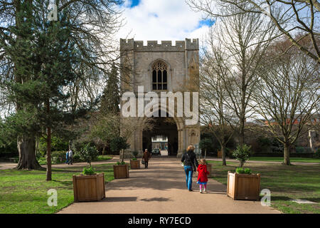 Bury St Edmunds Abbey Gardens, view of a parent and child walking through the Abbey Gardens towards the medieval Abbey Gate, Bury St Edmunds, UK - Stock Image