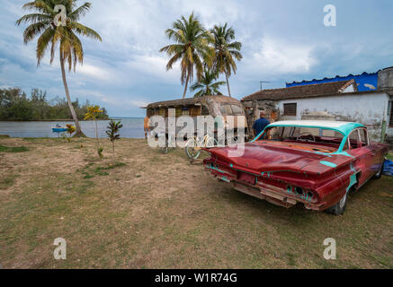 Plot of land beside house with derelict bus, used as a store, and old American car in the small town of Caleton on the south coast of Cuba, Caribbean - Stock Image
