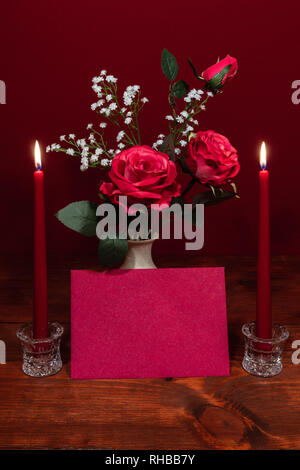 Beautiful pink roses in a vase accented with Baby's Breath flowers, Two lit ed candles in crystal holder and a card - Stock Image