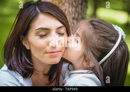 Adorable four years old cute little girl kisses her mother with love.Happy family on a summer meadow. little girl child baby daughter hugging and kiss - Stock Image