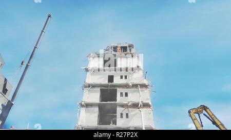 Crane and excavator tearing down a high rise building - Stock Image