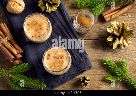 Eggnog with cinnamon in glasses over rustic wooden background with Christmas decor  - homemade traditional festive - Stock Image